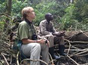 A volunteer and field guide watching Bahati and taking down data.